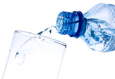 Pure water is poured from a bottle in a glass. The water flowing in a glass, is photographed in movement Stock Photos