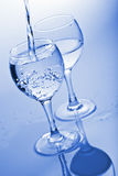 Pure water splashing into glass. Toned blue stock photography