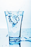 Pure water splashing into glass Stock Images