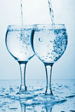 Pure water splashing into two glasses Stock Photography