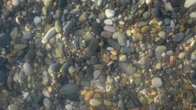 Pure water surface above polished stones, closeup view stock video footage