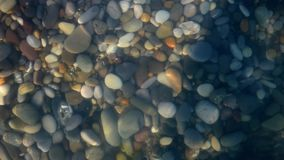 Pure water surface above polished stones. Closeup view. Underwater pebbles and sea waves. Sunny summer day. Natural background stock footage
