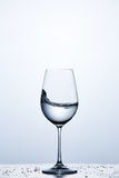 Pure water wave in the wine glass while standing on the glass with drapes against light background. Environmentally friendly product. Cleaner and useful water Stock Images