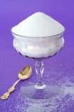 Pure White Granulated Sugar in a Vintage Glass on a Purple Backg royalty free stock photography