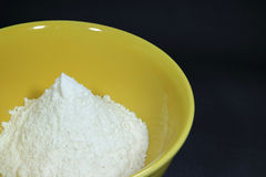 Pure white raw flour in yellow ceramic bowl, isolated on black background with free space for text Stock Photo