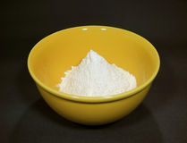 Pure white raw flour in yellow ceramic mixing bowl isolated on black background Royalty Free Stock Photography