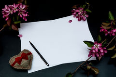 Pure white sheet of paper, pen and heart made of burlap and pink flowers on a black background Stock Image