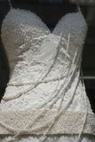 Pure white wedding gown with pearls. In a shop-window royalty free stock photos