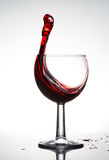 Pure wineglass with wave of brightly red wine on white background Stock Image