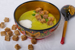 Puree in a bowl with,croutons, peas and sour cream. Puree with rusks peas and sour cream on a white tablecloth with rusks and a spoon closeup Royalty Free Stock Photo