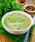 Puree green with spinach and spoon on board Royalty Free Stock Images