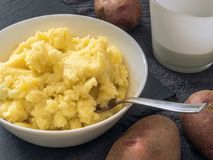 Puree. Mashed potatoes in a white plate, fresh potato, milk in a royalty free stock image