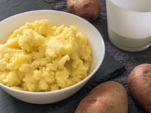 Puree. Mashed potatoes in a white plate, fresh potato, milk in a royalty free stock photo