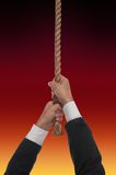 Purgatory. Man hanging at end of his rope over fire Royalty Free Stock Image