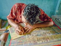 A young Indian man painting for sale at a countryside of India royalty free stock image