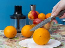 Purification of the orange with a knife before loading it into the blender. Cleansing orange for making lemonade Stock Photos