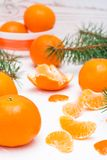 Purified mandarin slices, whole mandarins and fir branches. On a white table Stock Photography