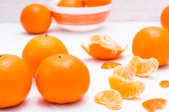 Purified mandarin slices and whole mandarins. On a white table Royalty Free Stock Images
