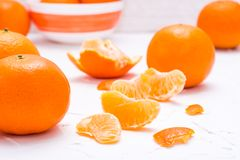 Purified mandarin slices and whole mandarins. On a white table Stock Photo