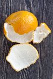 Purified yellow tangerines. Purified yellow white rind of tangerines on a natural wooden surface in black stock photos