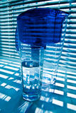 Purifying-filter and glass 2. Glass with water and water-purifying filter. Jalousie shadow on background. Blue colours stock photography