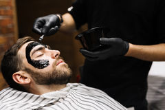 Purifying procedure. Barber applying purifying mask on his client face royalty free stock photos