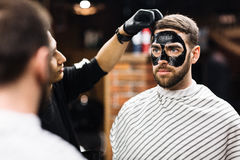 Purifying skin. Bearded men with purifying mask on his face looking in mirror royalty free stock image