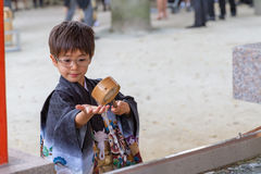A Purifying Wash. A boy of five, dressed in a formal kimono, washes his hands for purification upon entering a Japanese shrine for the 7-5-3 Ceremony, a rite of Royalty Free Stock Photo