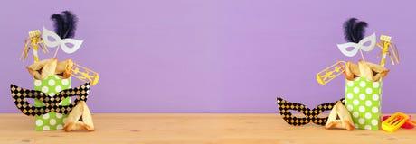Purim świętowania pojęcie & x28; żydowski karnawałowy holiday& x29; nad drewnianym stołu i purpur tłem zdjęcie stock