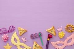 Purim świętowania pojęcie & x28; żydowski karnawałowy holiday& x29; nad menchiami, purpurowy drewniany tło Odgórny widok fotografia royalty free