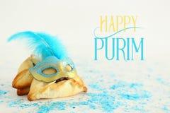 Purim berömbegrepp & x28; judisk karnevalholiday& x29; Traditionellt hamantaschen kakor med den härliga blåa och guld- maskeringe royaltyfria bilder