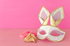 Purim celebration concept jewish carnival holiday with cute rabbit mask, noisemaker and hamantash cookies over wooden table royalty free stock image