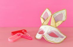 Purim celebration concept & x28;jewish carnival holiday& x29; with cute rabbit mask and noisemaker over wooden table. Animal background board card celebrate royalty free stock photography