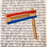 Purim Grogger. Traditional noisemaker (grogger) for the Jewish festival of Purim over page of hebrew scripture Royalty Free Stock Image
