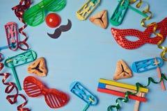 Purim-Hintergrund mit Karnevalsmaske, Parteikostüm und hamantaschen Plätzchen Stockbild