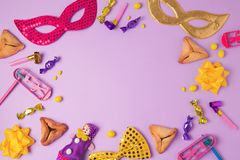 Purim holiday concept with carnival mask, hamans ears cookies and party supplies on purple background. Top view from above with copy space stock photos