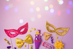 Purim holiday concept with carnival mask and party supplies on purple background with bokeh lights. Stock Images