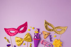 Purim holiday concept with carnival mask and party supplies on purple background. Top view from above. With copy space royalty free stock photography