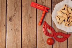Purim holiday concept celebration with clown mask and hamantaschen cookies on wooden background. Stock Photography