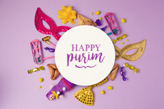 Purim holiday concept with white paper circle and party supplies on purple background. Stock Photos