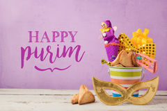 Purim holiday greeting card with carnival mask and gifts. Over purple background Stock Image