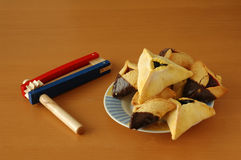 Purim icons. Hamantashen, traditional pastries for the Jewish holiday of Purim, along with a grogger, or traditional noisemaker for the holiday Royalty Free Stock Photos