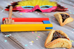 Purim Jewish holiday food and objects. Hamantaschen, wooden Purim gragger and carnival mask on a wooden table Royalty Free Stock Photography