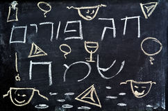 Purim Jewish Holiday. Happy Purim holiday greeting written in Hebrew with decorations on a chalkboard Stock Images