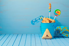 Purim traditional gifts with hamantaschen cookies, noisemaker and carnival mask. On blue background royalty free stock images