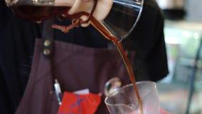 Puristkemeks Barista hällde konfektions- kaffe in i glass behållare för att tjäna som dess kunder till coffee shopbesökare stock video