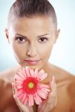 Purity. Portrait of beautiful female holding pink daisy with water drops on face Stock Photo