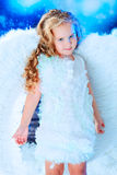 Purity. Beautiful little angel at a snowy background Stock Photography