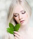 Purity. Beautiful young girl with healthy skin and green leaf Stock Images