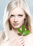 Purity. Beautiful young girl with healthy skin and green leaf Stock Image